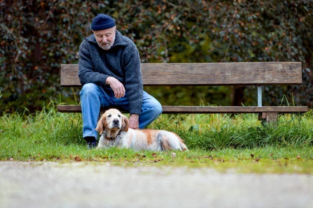 Alter Mann auf Parkbank mit Hund