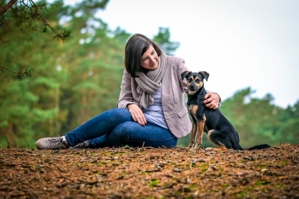 Frau sitzend mit Hund im Wald
