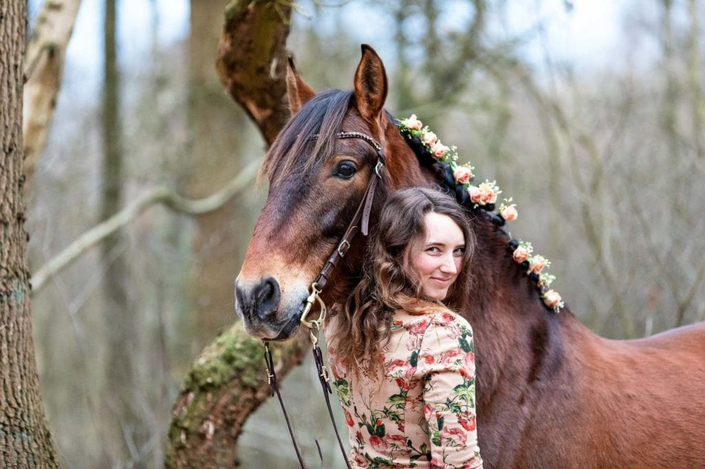 Frau mit Pferd in Kamera schauend