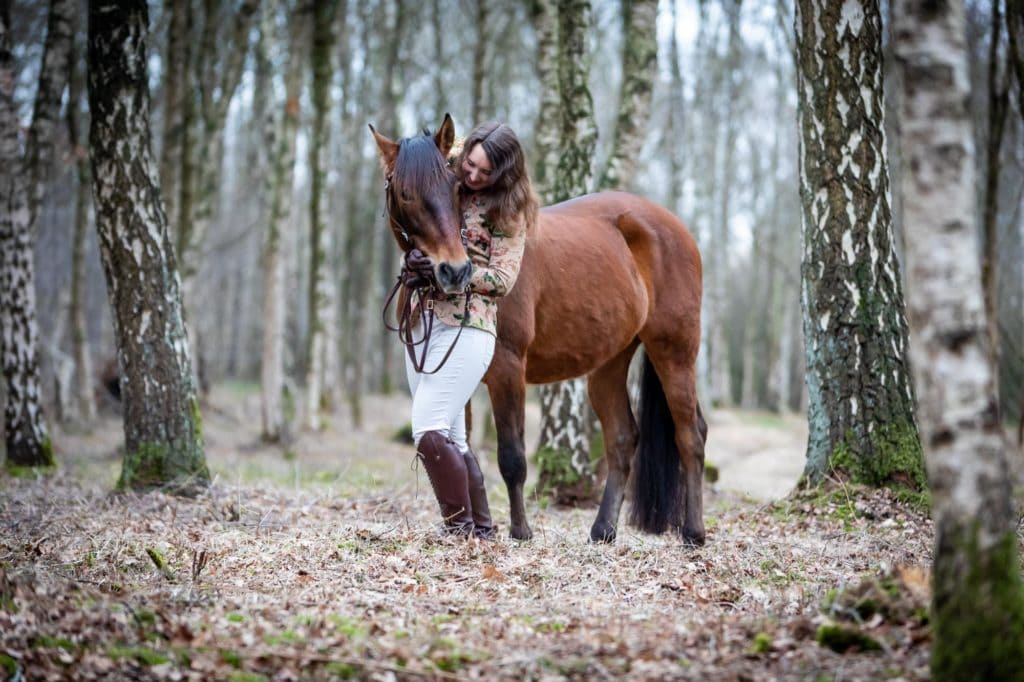 Frau mit Pferd im Birkenwald