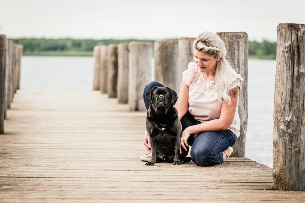 Hundefotografie Leipzig am See im Sommer Frau mit schwarzem Mops auf Steg