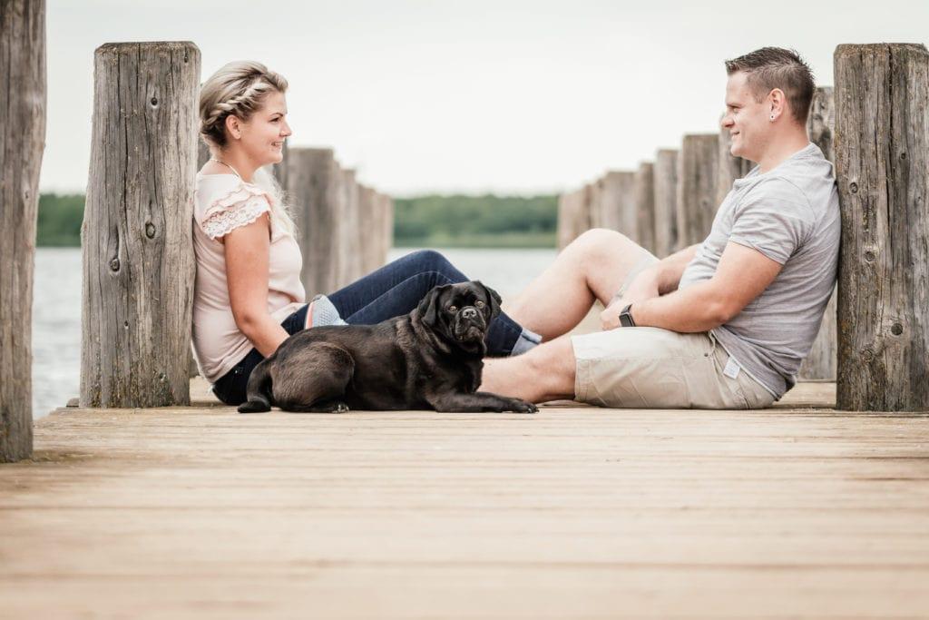 Hundefotografie Leipzig auf Bootssteg am See schwarzer Mops und Paar